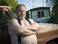 Overweight man with suspenders by truck Stock Photo - Premium Royalty-Freenull, Code: 640-02769476