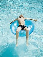 Young boy floating on life ring in swimming pool Stock Photo - Premium Royalty-Freenull, Code: 640-02769710