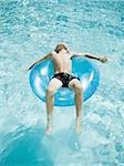 Young boy floating on life ring in swimming pool Stock Photo - Premium Royalty-Free, Artist: Dan Lim, Code: 640-02769710