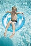 Young boy floating on life ring in swimming pool Stock Photo - Premium Royalty-Free, Artist: Guntmar Fritz, Code: 640-02769713