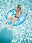Young boy floating on life ring in swimming pool Stock Photo - Premium Royalty-Free, Artist: Tim Mantoani, Code: 640-02769714