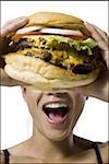 Woman eating a supersized hamburger Stock Photo - Premium Royalty-Free, Artist: Susan Findlay, Code: 640-02770319