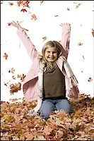 pile leaves playing - Young girl playing in fallen leaves Stock Photo - Premium Royalty-Freenull, Code: 640-02770477