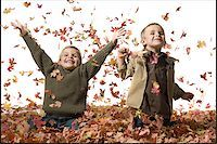 pile leaves playing - Young children playing in pile of fallen leaves Stock Photo - Premium Royalty-Freenull, Code: 640-02770479