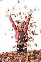 pile leaves playing - Young girl playing in fallen leaves Stock Photo - Premium Royalty-Freenull, Code: 640-02770514