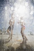 Two children playing at a sprayground Stock Photo - Premium Royalty-Freenull, Code: 640-02770639