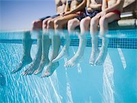Feet dangling in swimming pool Stock Photo - Premium Royalty-Freenull, Code: 640-02770646