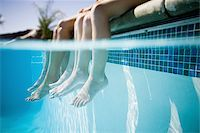 Feet dangling in swimming pool Stock Photo - Premium Royalty-Freenull, Code: 640-02770647