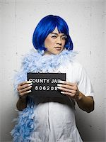 Mug shot of man in drag with blue wig and feather boa Stock Photo - Premium Royalty-Freenull, Code: 640-02770806