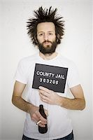 Mug shot of man with cigarette and beer bottle Stock Photo - Premium Royalty-Freenull, Code: 640-02770998