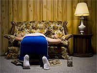 Man looking under sofa cushion Stock Photo - Premium Royalty-Freenull, Code: 640-02771068