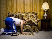 Man looking under sofa cushion Stock Photo - Premium Royalty-Freenull, Code: 640-02771069