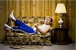 Man on sofa with pizza and TV remote Stock Photo - Premium Royalty-Free, Artist: Siephoto, Code: 640-02771077