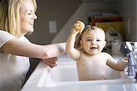 Woman bathing baby in sink Stock Photo - Premium Royalty-Freenull, Code: 640-02771482