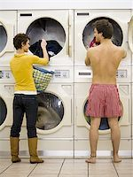 Woman and man in boxers removing clothing from dryers at Laundromat Stock Photo - Premium Royalty-Freenull, Code: 640-02771652