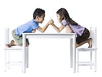 Boy and girl sitting at table arm wrestling Stock Photo - Premium Royalty-Freenull, Code: 640-02772735