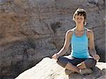 Woman sitting cross legged on rock outdoors doing yoga Stock Photo - Premium Royalty-Free, Artist: Robert Harding Images, Code: 640-02773197