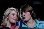 Boy and girl sharing beverage at movie theater
