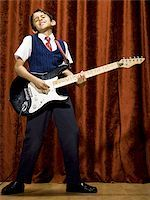preteen  smile  one  alone - Boy on stage playing electric guitar Stock Photo - Premium Royalty-Freenull, Code: 640-02774484