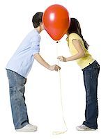preteen kissing - couple kissing behind a red balloon Stock Photo - Premium Royalty-Freenull, Code: 640-02778548