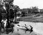 1940s 1950s PAIR OF BOYS IN ROWBOAT WITH COLLIE FISHING IN FARM AREA