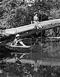 1940s 1950s PAIR OF BOYS IN STRAW HATS & CUFFED JEANS FISHING IN STREAM OFF OF FALLEN TREE & DIVING BOARD WITH STICK & STRING POLES