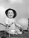 1960s BABY GIRL WEARING FISHING HAT HOLDING NET AND REEL FISHING GEAR INDOOR