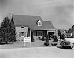 1950s MODEL HOME WITH SIGN OF LEVITT & SONS EXHIBIT HOME & PEOPLE MILLING ABOUT