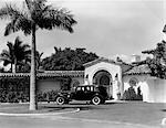 1930s CAR IN CIRCULAR DRIVEWAY OF TROPICAL STUCCO SPANISH STYLE HOME IN SUNSET ISLANDS MIAMI BEACH FL