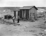 1930s POVERTY SCENE WITH 2 BOYS PLAYING IN FRONT OF SHACK DURING THE DEPRESSION