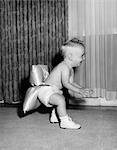 1950s LAUGHING BABY IN DIAPER AND SHOES LEARNING TO WALK WITH A PILLOW TIED TO HIS REAR END