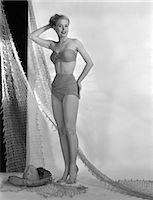 sandi model - 1950s GLAMOUR GIRL POSE IN STUDIO DRAPED WITH FISHING NET WOMAN IN TWO PIECE SWIM BATHING SUIT FASHION STRAPLESS BRA TOP    Stock Photo - Premium Rights-Managednull, Code: 846-02792137