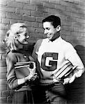 1950s 1960s TEENAGE COUPLE HOLDING BOOKS AND SMILING LEANING AGAINST WALL BOY WEARS VARSITY LETTER SWEATER