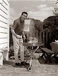 1960s HEAD-ON VIEW OF MAN BACKYARD PATIO COOKING STEAK ON GRILL