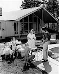1950s FAMILY SERVING HAMBURGERS BESIDE POOL IN BACKYARD COOKOUT