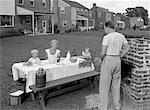 1950s FAMILY IN BACKYARD COOKING HAMBURGERS