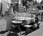1950s FAMILY IN BACKYARD COOKING HOT DOGS