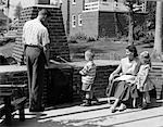 1950s FAMILY ON BRICKED BACKYARD PATIO LITTLE BOY COOKING HOT DOG ON SKEWER