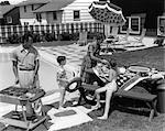1960s FAMILY OF 4 IN BACKYARD AT POOLSIDE FATHER BARBECUING & MOTHER & CHILDREN MAKING PREPARATIONS AT PICNIC TABLE