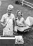 1950s COUPLE BACKYARD GRILL COOK HOT DOGS MAN WEARING APRON TOQUE & SKEWERED HOT DOG