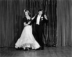 1940s COUPLE MAN AND WOMAN IN FORMAL WEAR BALLROOM DANCING ON STAGE