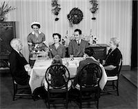 1940s TWO GENERATION FAMILY IN DINING ROOM BEING SERVED CHRISTMAS TURKEY BY MAID    Stock Photo - Premium Rights-Managednull, Code: 846-02792344