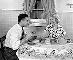1950s HUSBAND AND WIFE AT BREAKFAST EATING CEREAL & DRINKING COFFEE