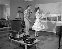 1950s LAUGHING TEENAGE COUPLE DANCING TO THE PHONOGRAPH PLAYING 78 RPM RECORDS IN LIVING ROOM    Stock Photo - Premium Rights-Managednull, Code: 846-02792414