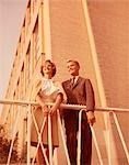 1960s YOUNG TEEN COUPLE SMILING OUTDOORS BY WROUGHT IRON RAILING AND BRICK BUILDING