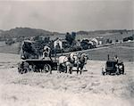 1930s PAIR OF MEN DUMPING HAY OFF OF BACK OF WAGON DRAWN BY TWO HORSES WITH MAN ON TRACTOR RIDING PAST THEM