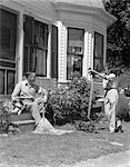1940s FATHER SITS ON PORCH STEPS HOLDING RAKE TALKING TO SON STANDING HOLDING LAWNMOWER BACKYARD WINDOW DOORWAY