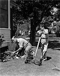 1930s 1940s FATHER & SON DOING YARD WORK THE BOY IS LEANING ON PUSH LAWN MOWER & MAN KNEELING WORKING IN FLOWER BED