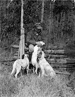1920s ELDERLY MAN SITTING WITH RIFLE RESTING AGAINST FENCE PETTING ONE OF THREE HUNTING DOGS    Stock Photo - Premium Rights-Managednull, Code: 846-02792988
