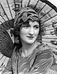 1920s PORTRAIT OF A WOMAN IN FRONT OF A JAPANESE PARASOL WEARING PEARLS AND A SILK PRINT HEADBAND